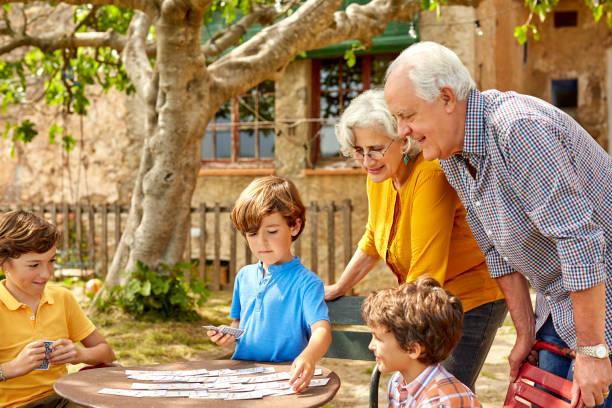 Famille avec petits-enfants et grands-parents en train de jouer dans le jardin