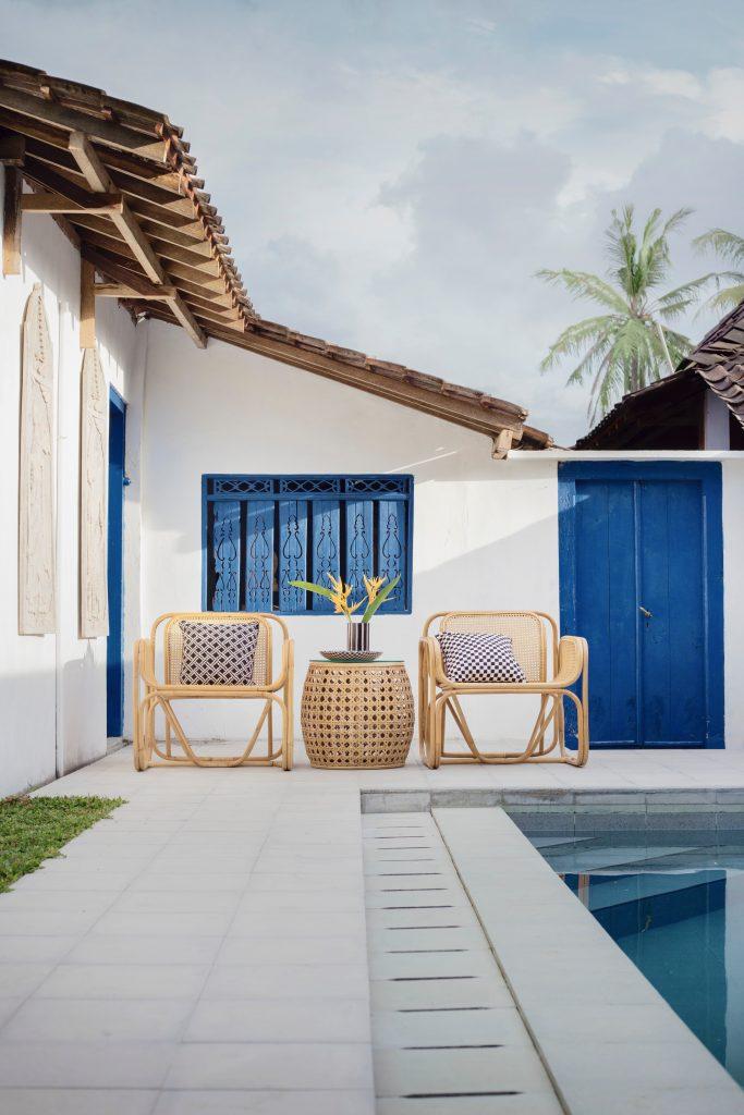terrasse avec piscine et salon de jardin en rotin