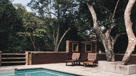 piscine extérieure avec revêtement de sol en béton et transats en bois